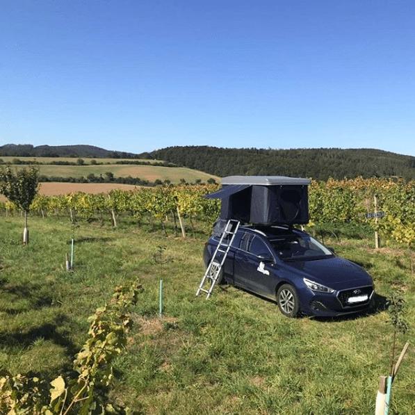 Rozložený střešní autostan s žebříkem v přírodě